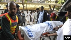 Rescue workers move a body at a hospital after a suicide bomb blast in Rawalpindi.