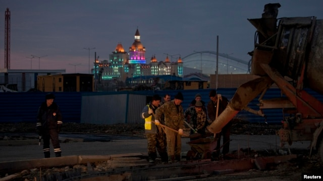 A Russian traffic officer watches construction workers near the main Olympic park in Sochi on January 7.