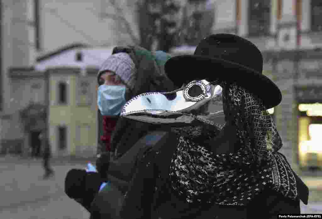 A woman wearing a protective mask stands beside a fellow pedestrian dressed in a plague-doctor's mask in the western Ukrainian city of Lviv. (epa-EFE/Pavlo Palamarchuk)