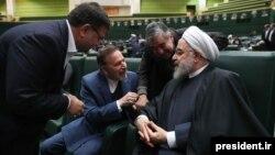 حسن روحانی در حال گفتوگو با دو تن از نمایندگان مجلس در جلسه ارائه بودجه ۹۹