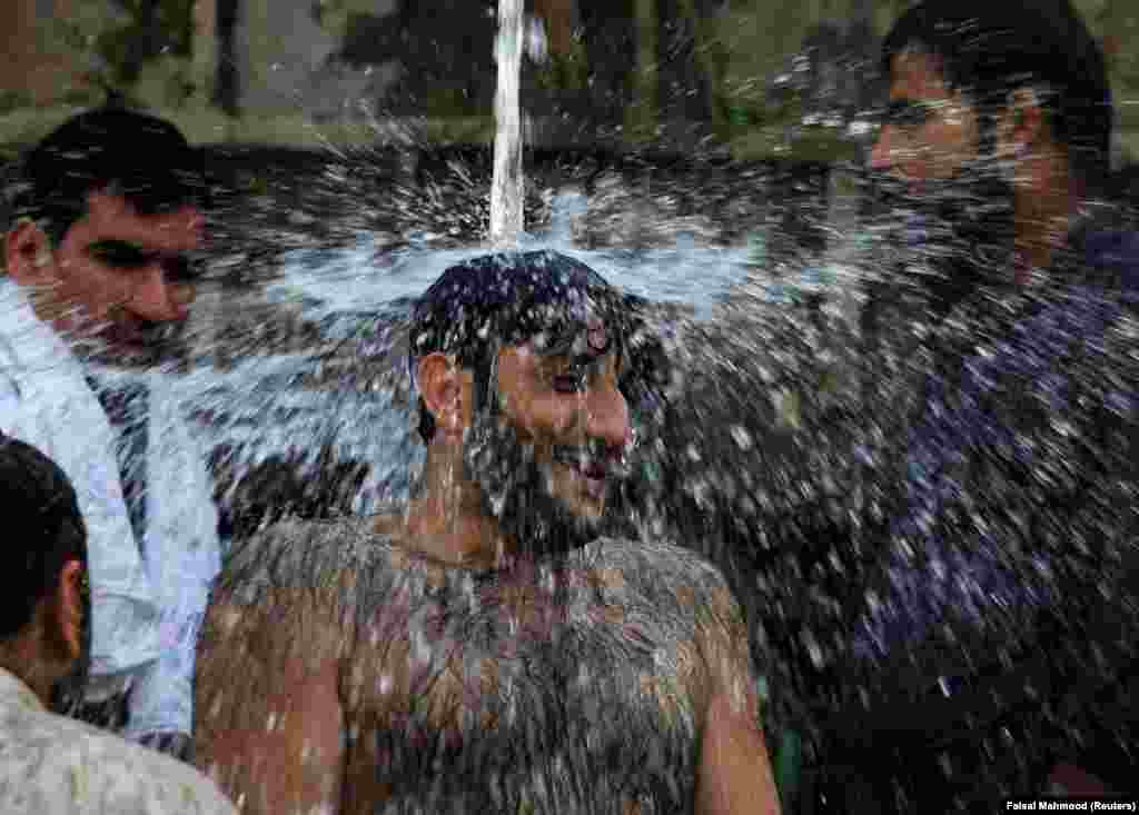 Men cool off with water coming out of a pipe during a heatwave in Islamabad, Pakistan. (Reuters/Faisal Mahmood)
