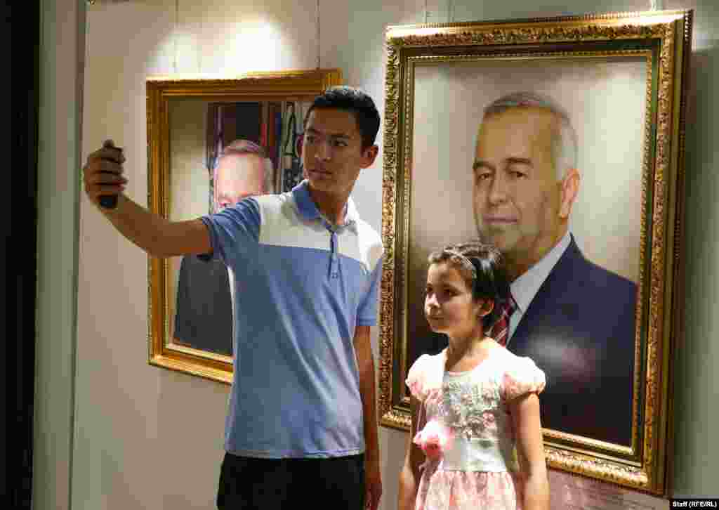 Young visitors grab a selfie with a canvas Karimov.