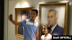 Музейге келушілер Каримов портреті жанында селфиге түсіп жатыр