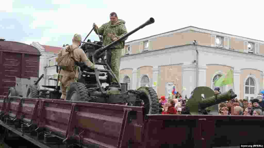 На платформе поезда – орудия и одетые в советскую военную форму актеры. Они фотографируются с местными жителями, поднимают на руки детей и размещают их поближе к орудиям