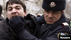 """A policeman detains an opposition activist in Baku. The report says Azerbaijan's government unleashed a """"new wave of repression and intimidation"""" in the past year."""