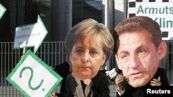 Demonstranti sa maskama sa likom njemačke kancelarke Angele Merkel i predsjednika francuske Nicolasa Sarkozyja