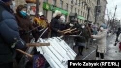 Таяқ ұстаған наразы жұрт милиция жасағына қарсы тұр. Киев, 20 қаңтар 2014 жыл.