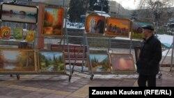 Прохожий смотрит на картины на Арбате. Алматы, март 2013 года.