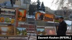 Арбаттағы суреттерді тамашалап өтіп бара жатқан адам. Алматы, 12 наурыз 2013 жыл.