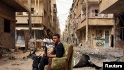 Një pjesëtar i forcave opozitare siriane e mban armën e tij deri rri i ulur në mes të rrugës në Deir al-Zor, 02 Prill 2013