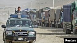 A police vehicle drives past trucks carrying voting materials in the Afghan capital, Kabul, on September 16.