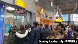 Купившие билеты на рейсы Bek Air пассажиры в очереди у кассы в алматинском аэропорту. 28 декабря 2019 года.