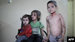 Wounded Syrian children wait to receive treatment at a hospital following a reported air strike on the rebel-held northwestern city of Idlib on September 29.
