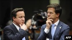 """Kryeministri britanik, Dejvid Kameron, dhe ai holandez, Mark Rut, para nisjes së punimeve të samitit të BE-së, ku është rënë dakord për një marrëveshje të re për shpëtimin e euros, përkatësisht për """"kompaktin e ri fiskal"""". Bruksel, 9 dhjetor 2011."""