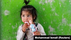 An internally displaced Afghan girl plays outside her shelter in Kabul in May.