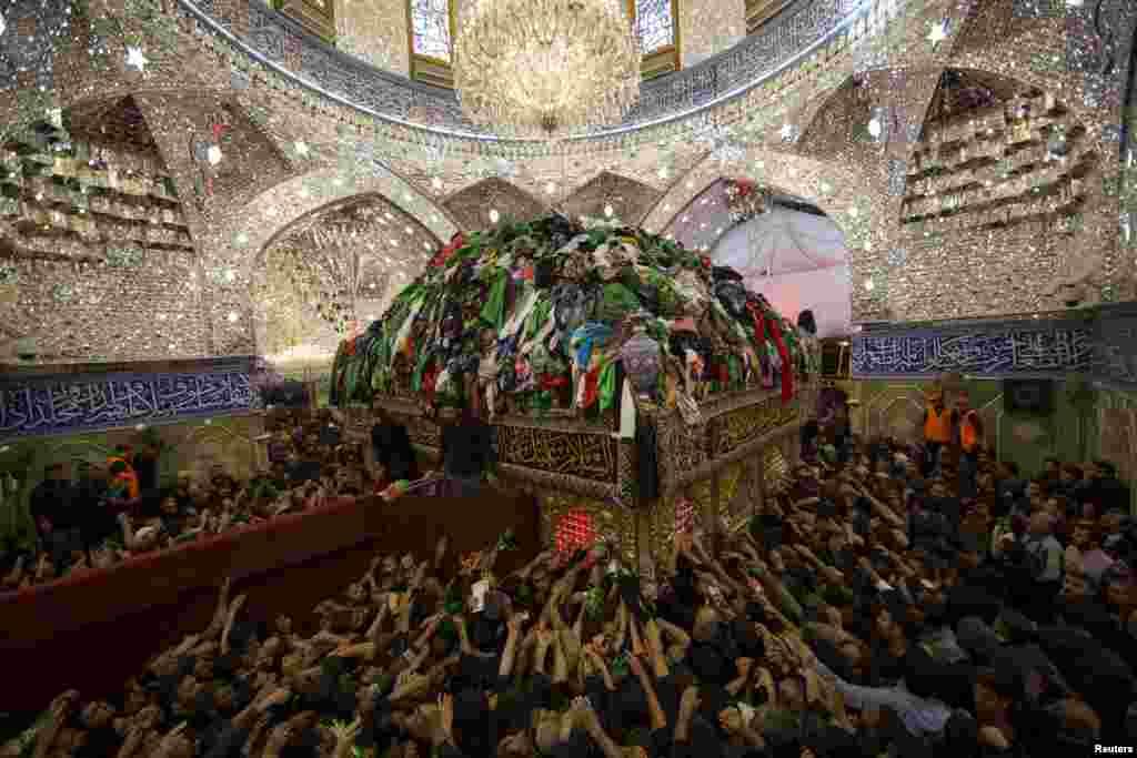 Шыіцкія паломнікі працягваюць рукі да магілы Імама аль-Абаса ў ягоным маўзалеі падчас адзначэньня сьвята Арбаін у сьвятым шыіцкім горадзе Карбала, Ірак, 3 сьнежня. (Reuters/Ahmad al-Husseini)