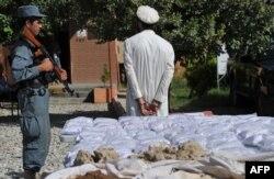 Полицей тұтқындалған есірткі сататын адамды күзетіп тұр. Ауғанстан, 19 қыркүйек 2013 жыл.