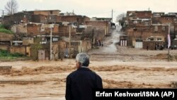IRAN -- A man watches as floodwaters hit the city of Khorramabad in the western province of Lorestan, April 1, 2019