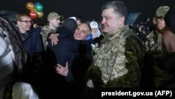 Ukranian President Petro Poroshenko (right) looks on during meetings between former prisoners and relatives at a military air base in Kyiv on December 27.