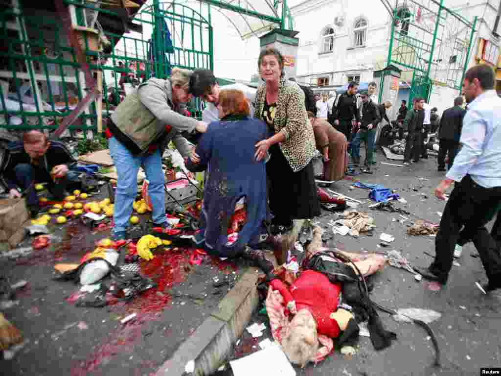 Люди помогают пострадавшим при взрыве на центральном рынке Владикавказа, 9 сентября 2010