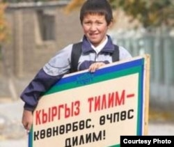 Мальчик с плакатом о достоинствах кыргызского языка. Иллюстративное фото.