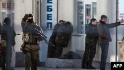 Російські військові беруть у полон офіцерів української армії після штурму фотограметричного центру в Сімферополі. Одного українського військового під час штурму було вбито