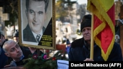 A man holds a portrait of late dictator Nicolae Ceausescu at the tomb of Ceausescu and his wife, Elena, at Ghencea Cemetery in Bucharest on January 26.