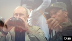 Ресей президенті Владимир Путин дүрбімен әскери жаттығу барысын қарап отыр. Ресей, 17 қыркүйек 2012 жыл.