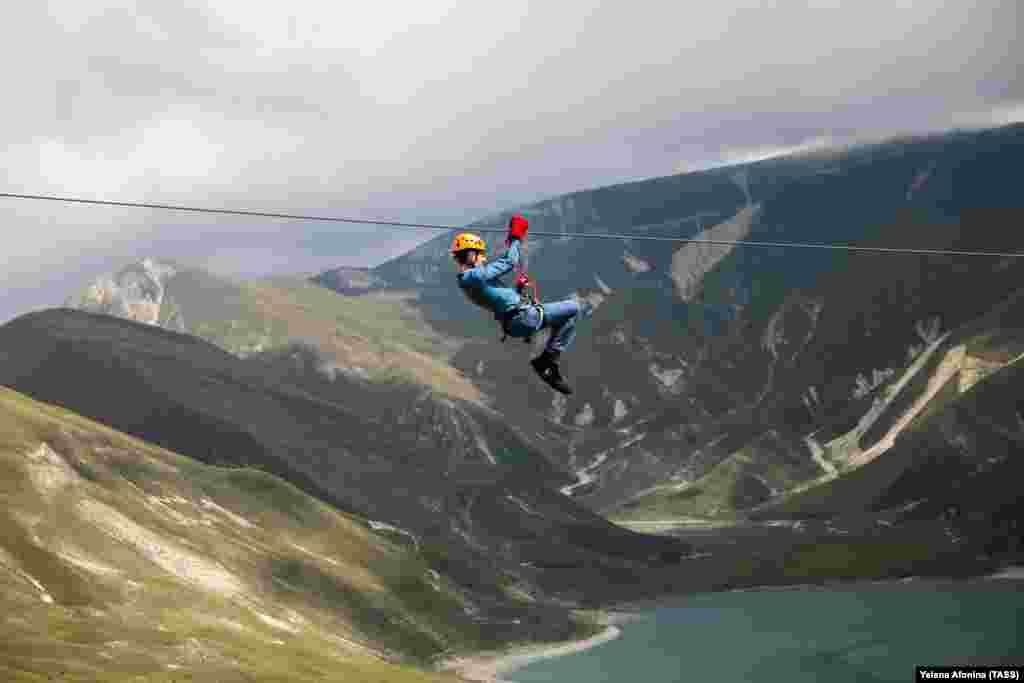 A man rides a zip line on Lake Kezenoyam in the Caucasus Mountains in Russia's Chechnya region. (TASS/Yelena Afonina)