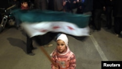 A Syrian girl waves an opposition flag during an antigovernment protest in Al-Qusayr on February 27.
