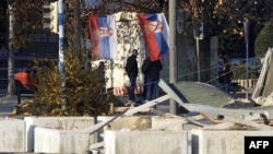 Ethnic Serbs stand in front of a barricade in the divided town of Mitrovica, in northern Kosovo.