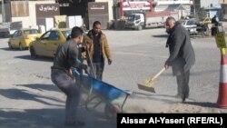 مواطنون ينظفون شارعاً في النجف