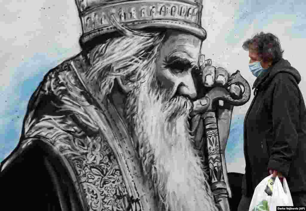 A woman wearing a mask against the spread of the coronavirus walks past a mural depicting late Serbian Orthodox Church Bishop Amfilohije in Belgrade. (AP/Darko Vojinovic)