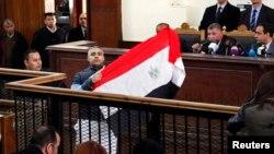 Мухаммед Фахми сот төрагасы менен сүйлөшүп жатканда Египеттин желегин көрсөтүүдө. 12-февраль 2015