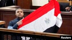 Журналист телеканала Al-Jazeera Мохаммед Фахми с национальным флагом Египта в зале суда в Каире. 12 февраля 2015 года.