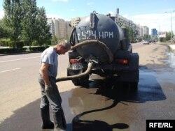 Цистерналы көлікпен су сорып тұрған жұмысшы. Астананың сол жағалауы, 2 тамыз 2013 жыл.