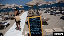 Жена минава покрай табло, призоваващо за спазване на дистанция на плаж на остров Кос, където миналата седмица имаше увеличение на броя на новозаразени с коронавирус