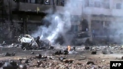 A video grab allegedly shows a burning vehicle and gas cylinders, mainly used for cooking, strewn across a street after a mortar shell struck a gas depot store in the central restive city of Homs on March 20.