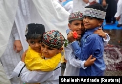 INDIA - Copiii se salută după ce au făcut rugăciuni Eid al-Fitr, care marchează sfârșitul lunii sfinte a postului Ramadan, în Mumbai, India, 26 iunie 2017.