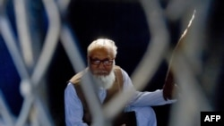 Bangladeshi Jamaat-e Islami party leader Motiur Rahman Nizami sits inside a van while being taken to a prison after being sentenced at the International Crimes Tribunal court in Dhaka, October 29, 2014