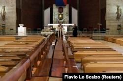 Священик освячує труни, які накопичуються в церкві через велику кількість смертей