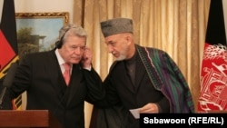 Afghan President Hamid Karzai (right) speaks with German President Joachim Gauck during a press conference at the Presidential Palace in Kabul on December 18.