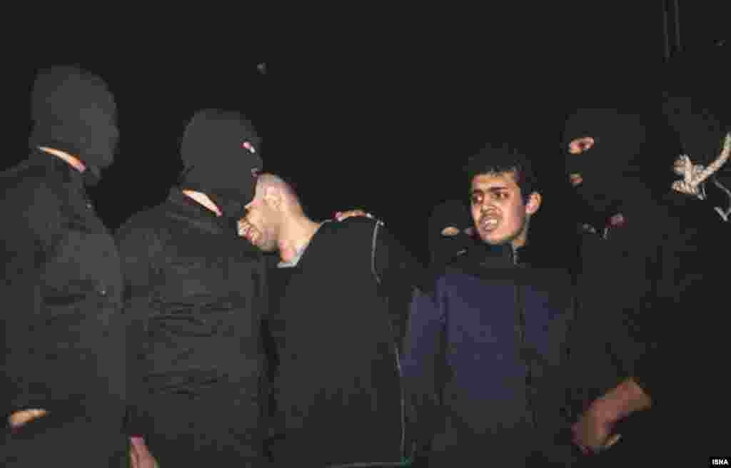 "Alireza Mafiha rests his head on the shoulder of an executioner, who has his arm around him, moments before his death by hanging in Tehran. Mafiha was publicly executed along with Mohammad Ali Sarvari (second from right) after a video was posted on YouTube in December showing them robbing and stabbing a man on a street in Tehran. The man survived. Judiciary chief Ayatollah Sadeq Larijani called it a ""moharebeh"" crime, which Iran's legal code defines as ""defiance of God,"" or the state, and is punishable by hanging. (ISNA)"