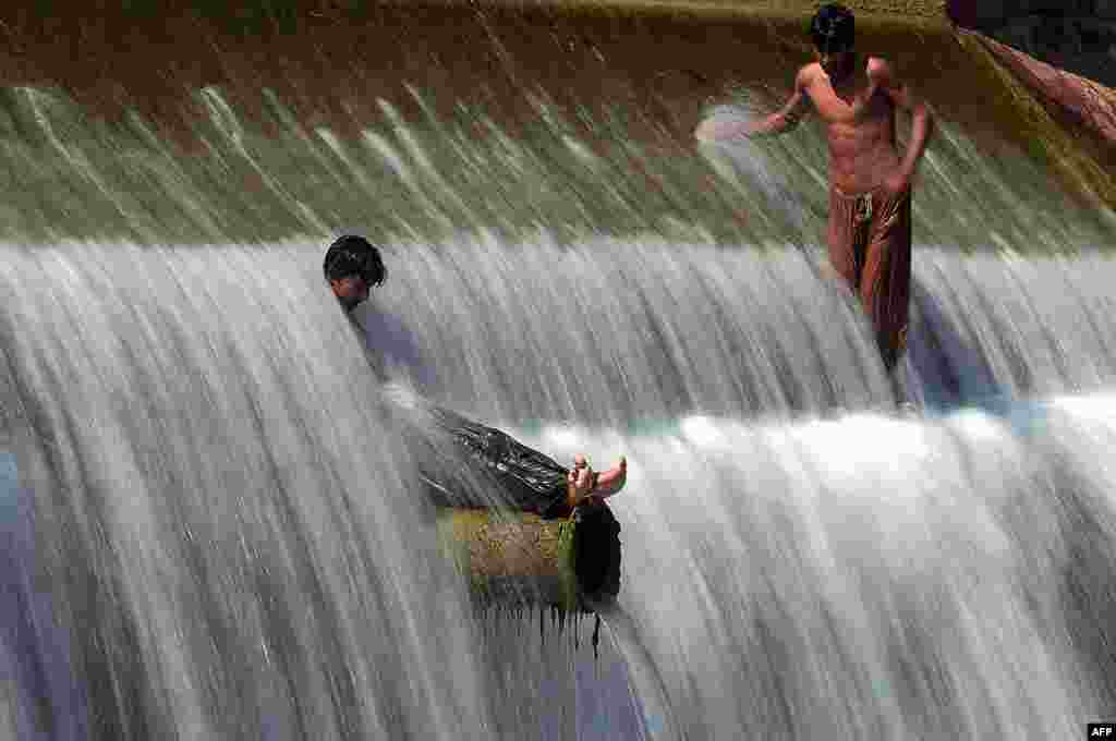 Pakistani youths cool off in a stream during hot weather on the outskirts of Islamabad. (AFP/Aamir Qureshi)