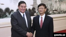 SNB chief Rustam Inoyatov (left) meets with an official in China in October 2014.