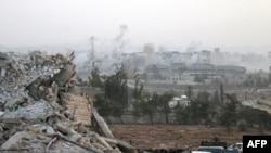 Syrian regime forces gather at the Kindi Hospital as smoke billows following air strikes on Aleppo on October 2.