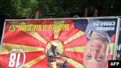 A man rides his bicycle past an upside-down billboard of opposition leader Ljube Boskovski in downtown Skopje