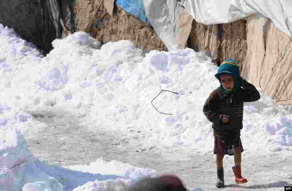 An Afghan boy from Helmand Province stands outside a snow-strewn mud shelter at the Charhi Qambar refugee camp on the outskirts of Kabul on February 6. (AFP)