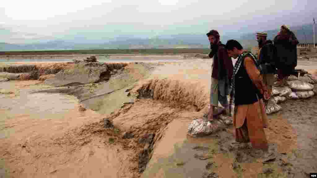 Locals look on as flash floods continue in the northern Afghan province of Baghlan on April 23. (EPA/Naqeeb Ahmed)