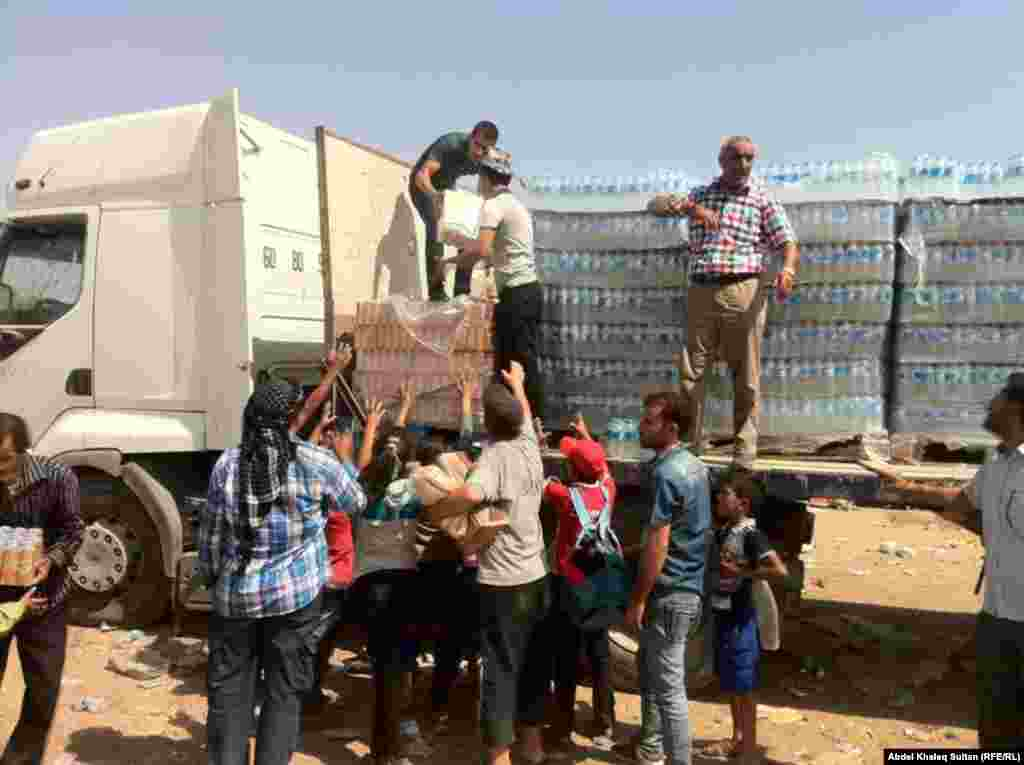 Refugees receive food and water in the border village of Sihela, in Iraq's autonomous Kurdish region.